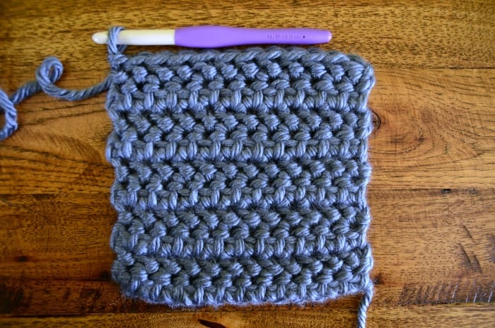 crocheting a pocket with blue super bulky yarn