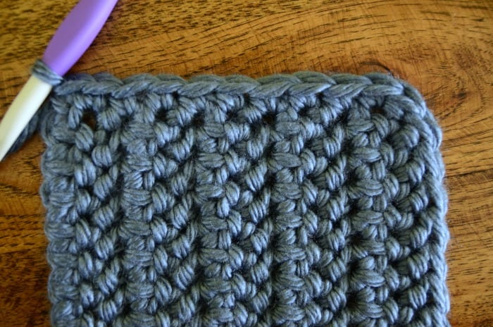 crocheting around a pocket with super bulky blue yarn