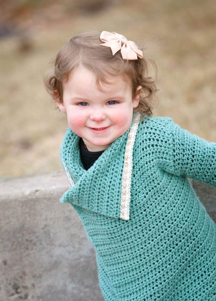 Little girl wearing a teal crocheted blanket cardigan with bow in hair