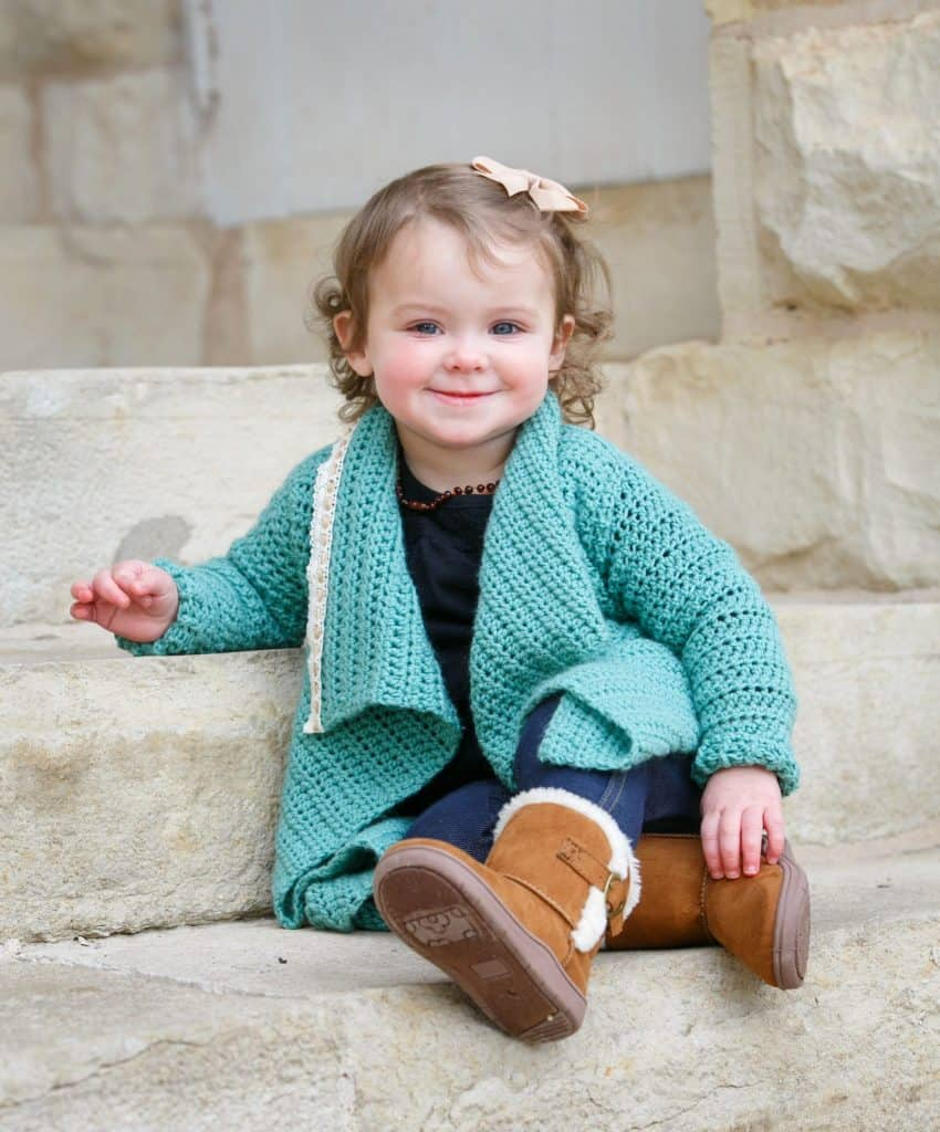 Small girl modeling a teal blanket cardigan for free crochet pattern