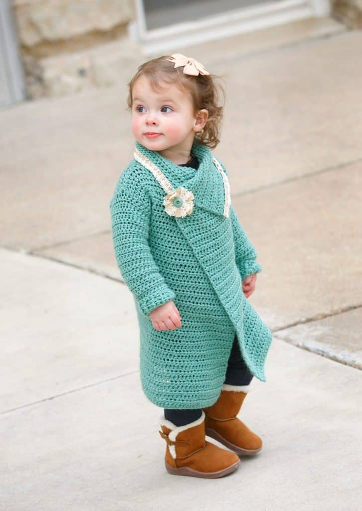 Baby girl wearing teal blanket cardigan with flower and lace edging