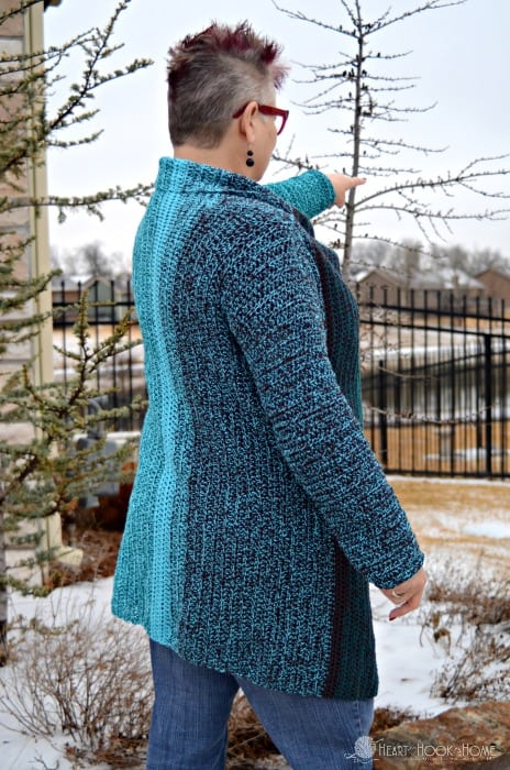 woman pointing wearing a crocheted sweater