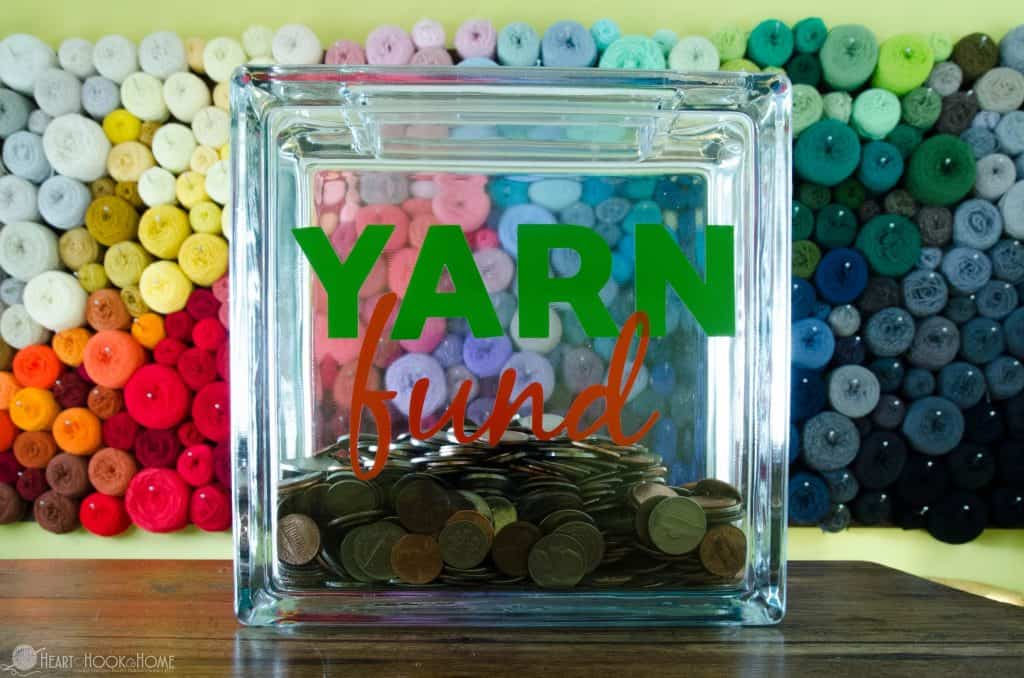 Yarn Fund piggy bank in front of a yarn wall