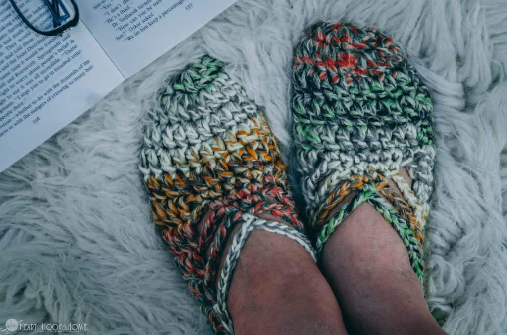 Multi-colored chunky yarn crochet slippers on a rug with book and glasses
