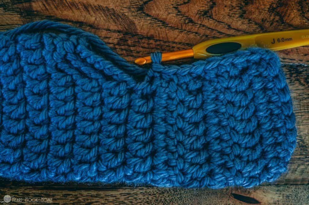 Blue yarn and crochet hook making a chunky slipper
