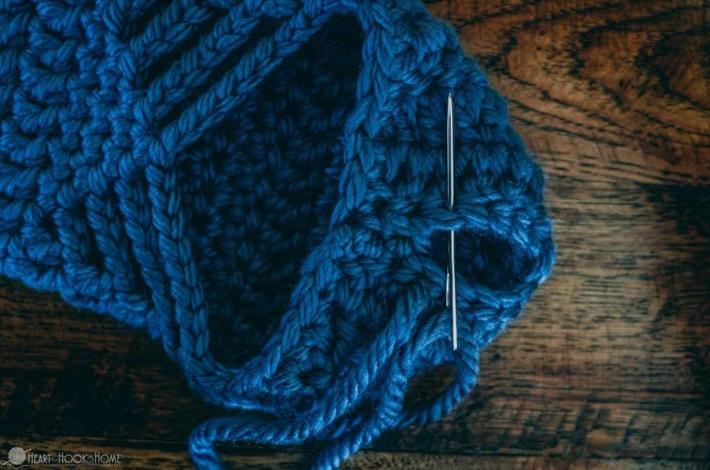 Sewing up the heel of crochet slipper using blue chunky yarn