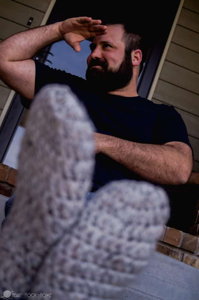 Man looking off into the distance wearing crocheted slippers
