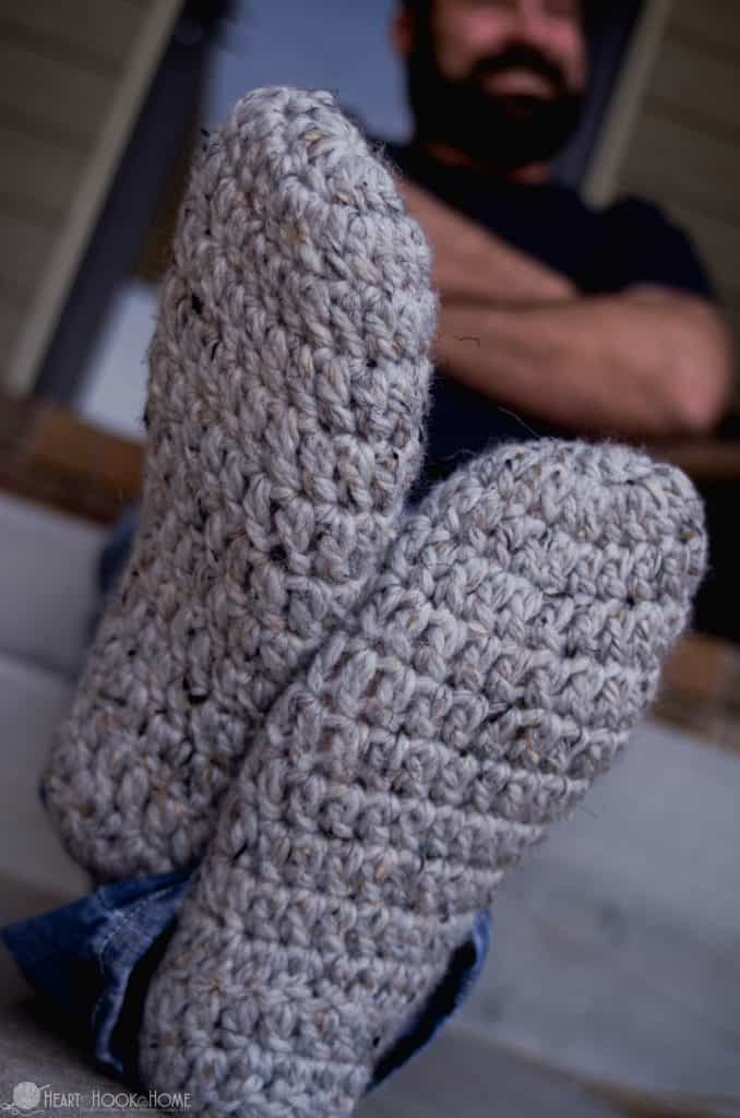Bearded man wearing crocheted slippers