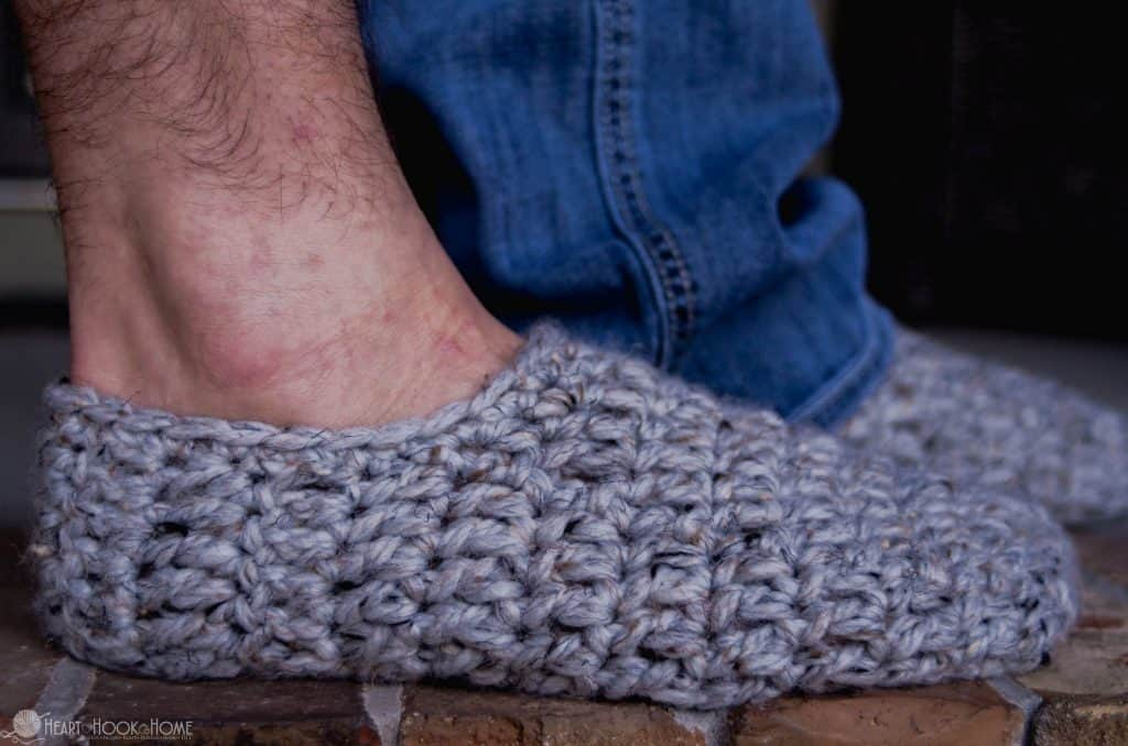 man's leg and foot standing in crocheted slippers